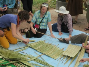 Tour participants learn how to sew palm leaves to make a thatched roof.