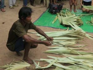 Palm leaves are cut in preparation for sewing,  to create a thatched roof.